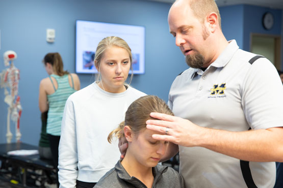 Faculty member working with two students in Physical Therapy class.