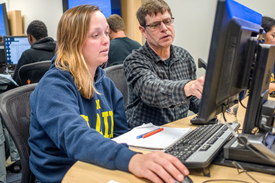 Faculty working with a student in a Computer Science & Information Systems class.