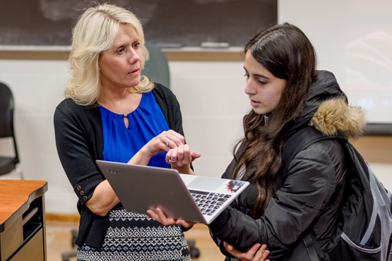 Faculty member helping a student during a psychology class.