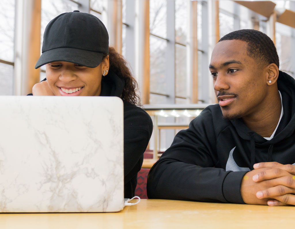 Two students working on a laptop.