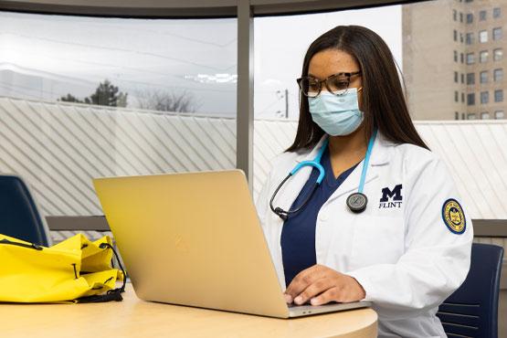 School of Nursing student working on laptop.
