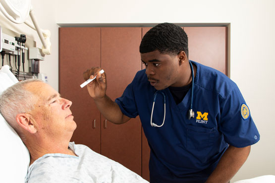 School of Nursing student working with a patient.
