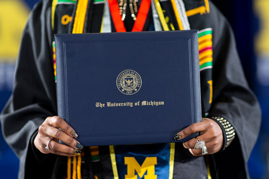 Graduate holding diploma cover.